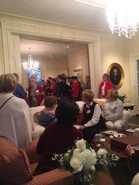 A room full of women listening to a men's choir singing